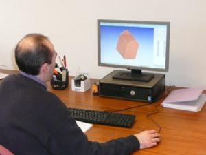 Personne qui travaille sur un ordinateur afin de concevoir un emballage sur-mesure